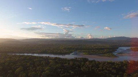 Aerial view of rainforest beside Rio Napo illuminated by the last rays of the evening sun. Napo province in the Ecuadorian Amazon. Cordillera de Galeras and Sumaco Volcano in distance.