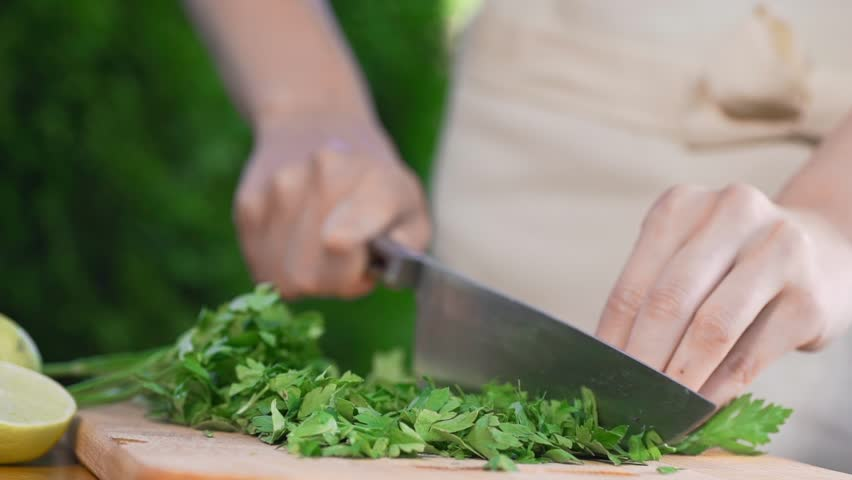 The Cook Slices Parsley On Wooden Board By Big Knife Cooking Outside