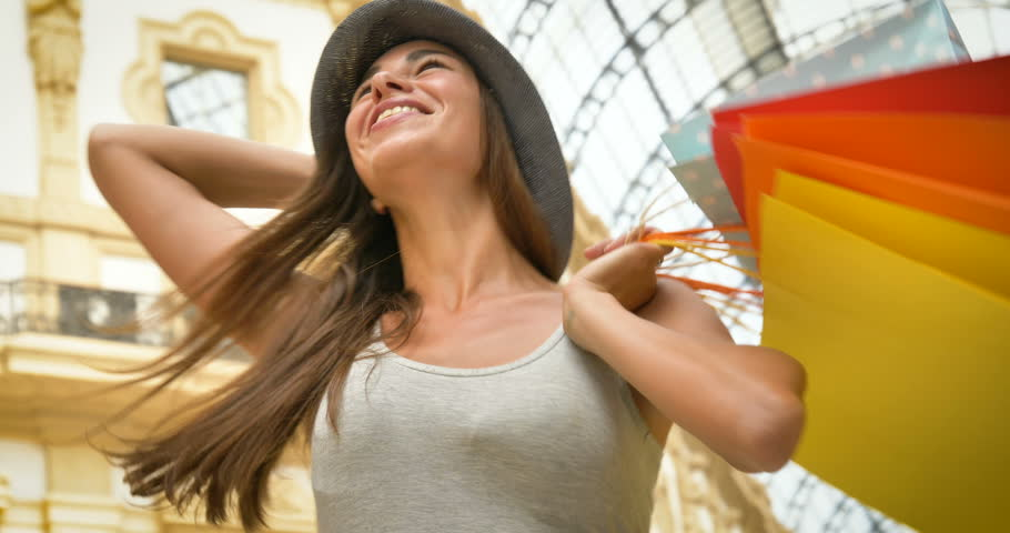 Beautiful young tourist girl (woman) in Milan, shopping, wearing a hat, new clothes, happy smiling, background Milan gallery. Concept: tourism, love travel, communication, freedom, love life, shopping