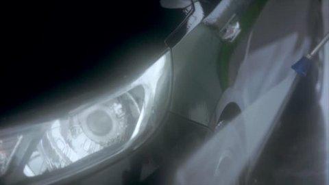 Man washing tyres on the car wash self-service. Car washing process. Water spray.