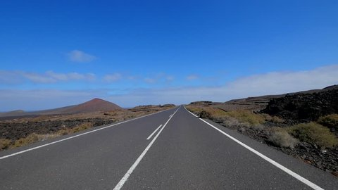 POV: Driving in the desert with blue sky on the island of Lanzarote, Canary Islands. Spain, Europe.