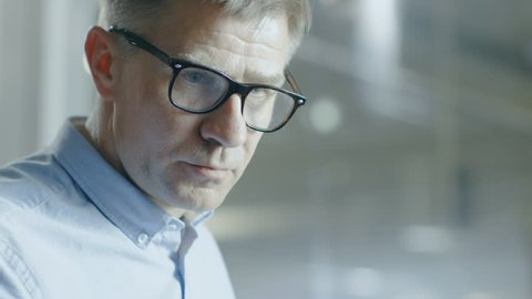 Close-up Shot of Senior Automotive Designer with Rake Sculpts Futuristic Car Model from Plasticine Clay.He Works in a Special Studio Located In a Large Car Factory.Shot on RED EPIC-W 8K Camera