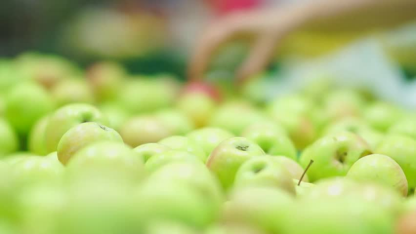 Customers select green apples in supermarket
