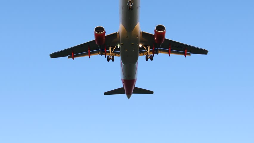 Airplane Flying Overhead against Blue Sky - Taking Off / Landing