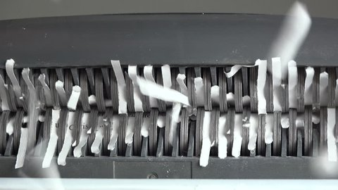 Cut paper strips tumble from paper shredder blades, fall onto camera lens. 4K UHD 3840x2160