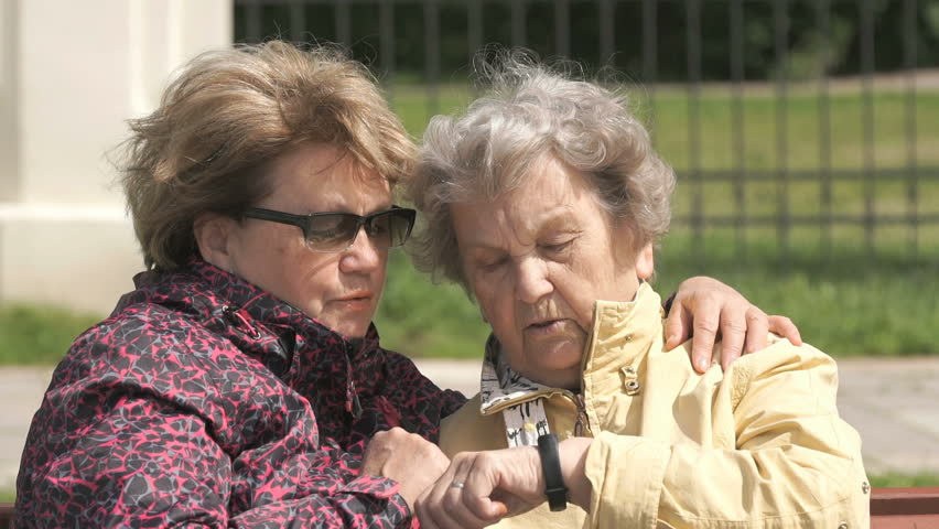 Two women sit and talk outdoors. One woman aged 80s dressed in yellow jacket looks at the results of physical activity using a wristband fitness tracker outdoors