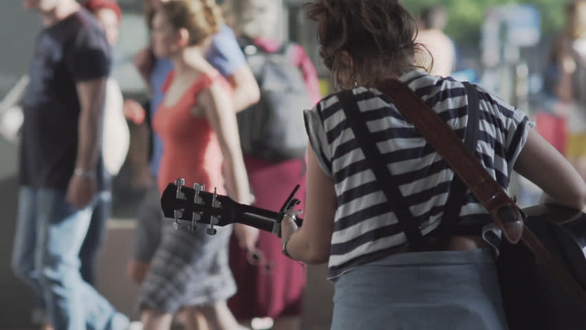Unidentifiable Young Woman Playing Guitar On A Busy Shopping Street In Berlin In Summer. Slow Motion Shot.