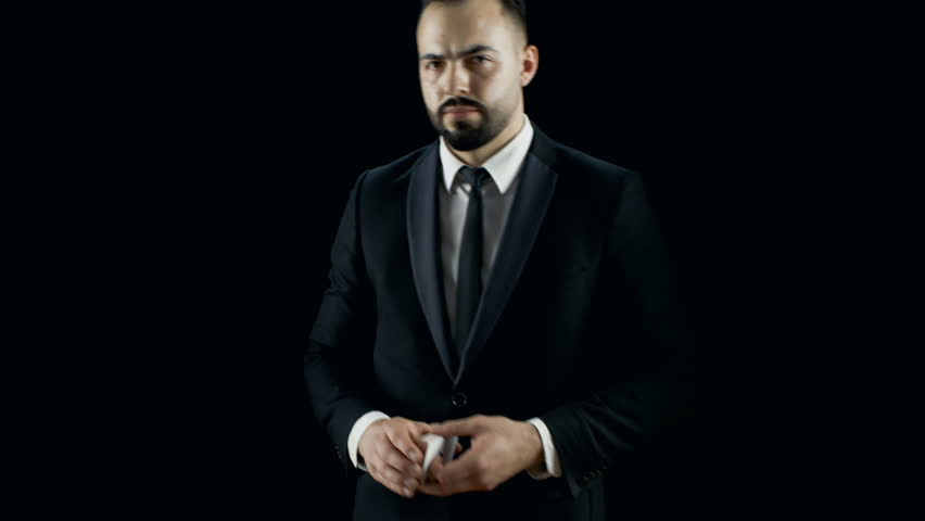 Magician in a Dark Suit Steps into the Light does Sleight of Hand Fan out Card Trick. Background is Dark Black. Shot on RED EPIC-W 8K Helium Cinema Camera. | Shutterstock HD Video #28898086