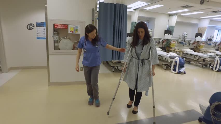 Nurse helps a female patient on crutches walk through