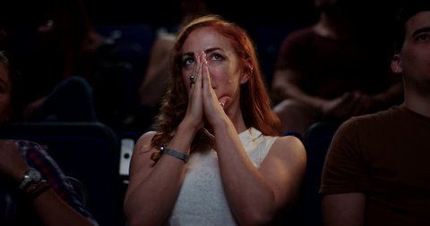 Young woman at the cinema reacting to a scary scene in a horror movie