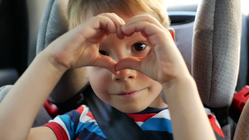 Little boys hands making heart shape gesture while sitting in car seat in summer evening. Young boy looking through the heart from hands to the camera. Child hands showing heart. Happy family concept