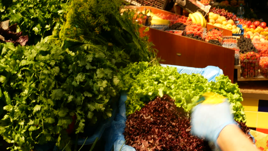 Women sprinkles a lot of parsley, spinach, basil, rennel, dill, tarragon, and melissa at the counter at the market close-up