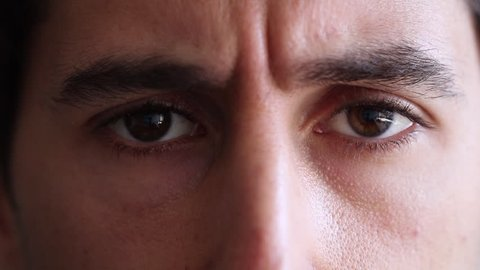 Man closes eyes and opens them up again. Man frowns with concern while closing and opening eye lids