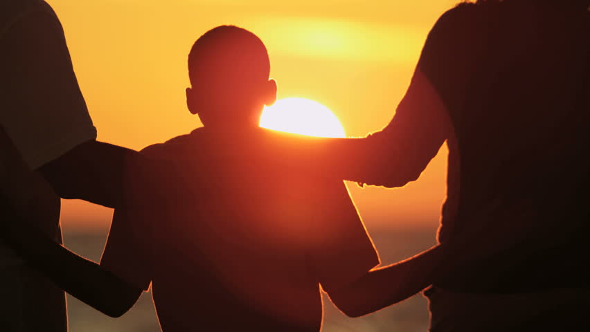 silhouette of young african american family spending time together on beach holiday at sunset red epic
