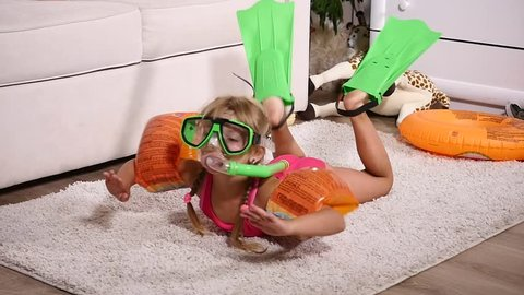 A girl in a underwater mask and flippers swimming in the room.