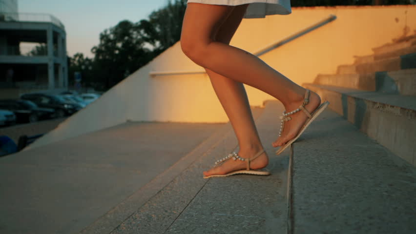 Woman legs in fashionable sandals going down the stairs outrdoor. Slow motion. Summertime
