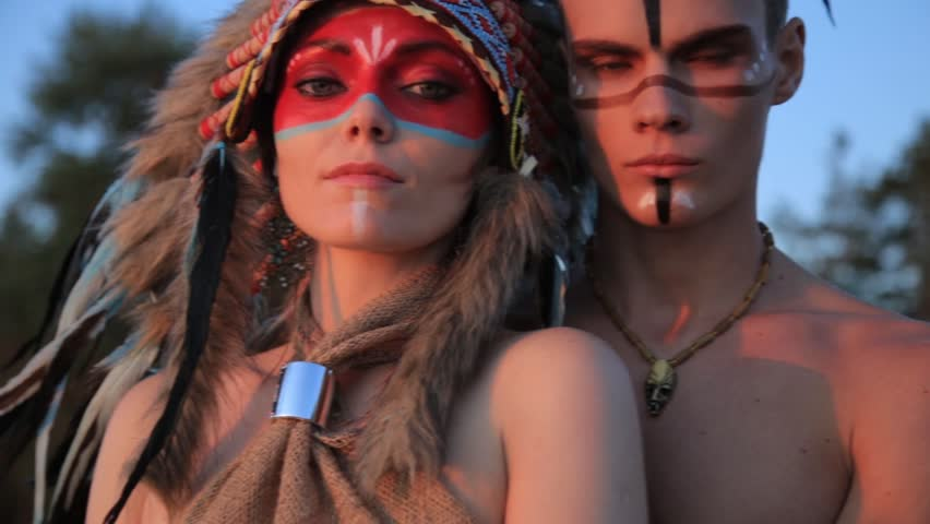 Beautiful native american Indian man and woman in traditional dress smiling at the sea beach at sunset.