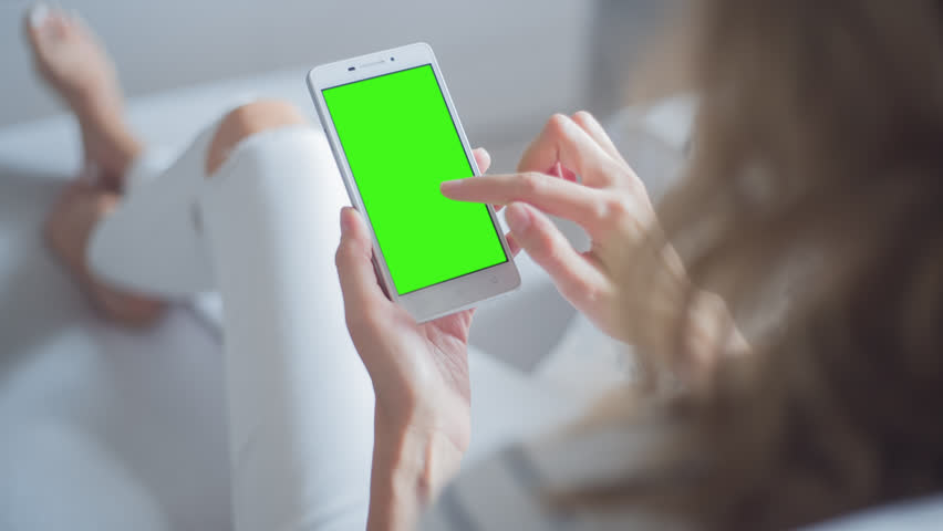 Young Woman in white jeans sitting on couch uses SmartPhone with pre-keyed green screen. Few types of gestures - scrolling up and down, tapping, zoom in and out.    Shutterstock HD Video #29065318