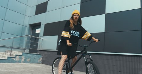 Young stylish Caucasian female in hockey style jersey riding her bicycle against grey wall background. 4K UHD RAW edited footage