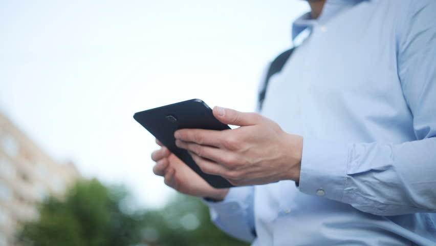 Man hands holding moving tablet vertically horizontally turning black laptop device outside blue shirt holds wireless technology modern closeup side view using gadget standing horizontal position | Shutterstock HD Video #29080846
