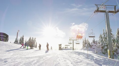 A few skiers ski by as others can be seen on a chairlift and groomed runs on Grouse Mountain near Vancouver, Canada. 4k. Slow motion.