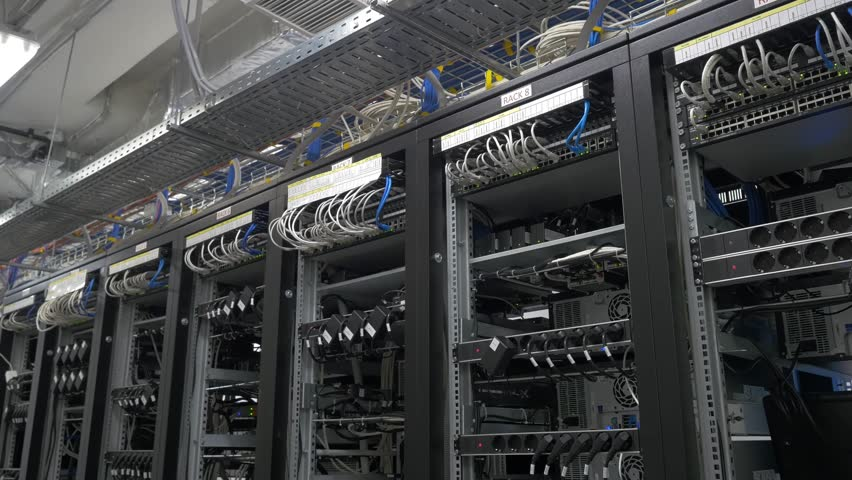 Row of bitcoin miners set up on the wired shelfs. Computer for Bitcoin mining. cables plug to motherboard for mining machine. Cryptocurrency computer with many peripheral slots | Shutterstock HD Video #29086336