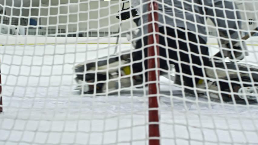 4k00 15pan From Behind Net Of Hockey Goalie Guarding Net Then