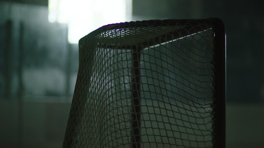 slap shot being taken in hockey arena hockey puck goal score scoring in net slow motion