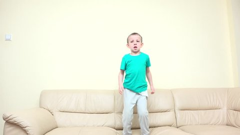 Happy child jumping on sofa, rise up hands, enthusiastic dance, free childhood, kid tired falling down