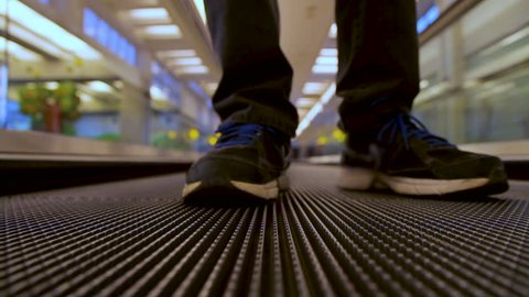 Closeup front view on man legs traveler using moving flat escalator at airport terminal