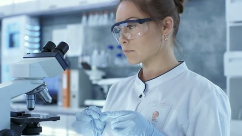 Medical Research Scientists putting Slides in Place and Looking at Samples Under Microscope. She Works in a Bright Modern Laboratory. Shot on RED EPIC-W 8K Helium Cinema Camera.