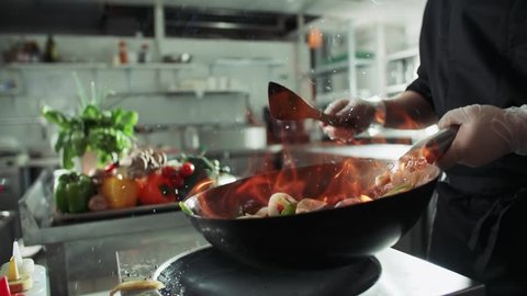 close-up of a chef working the wok with flames roasting mixed colorful vegetables tossing them , restaurant kitchen , slow motion