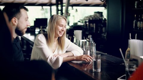 Young friends who sit on bar stools near a boron counter communicate with each other, a pretty blonde tells a funny story and smiles