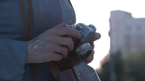 Girl's hands hold the vintage old film camera. Girl camera shutter clicks close up