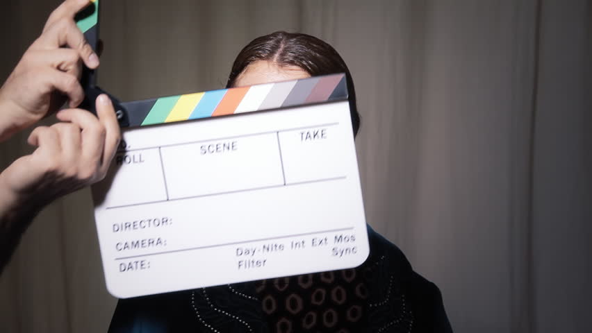 A movie slate or clapperboard clapping over the face of a funny ugly woman. She smiles and shows her profiles like at an audition.