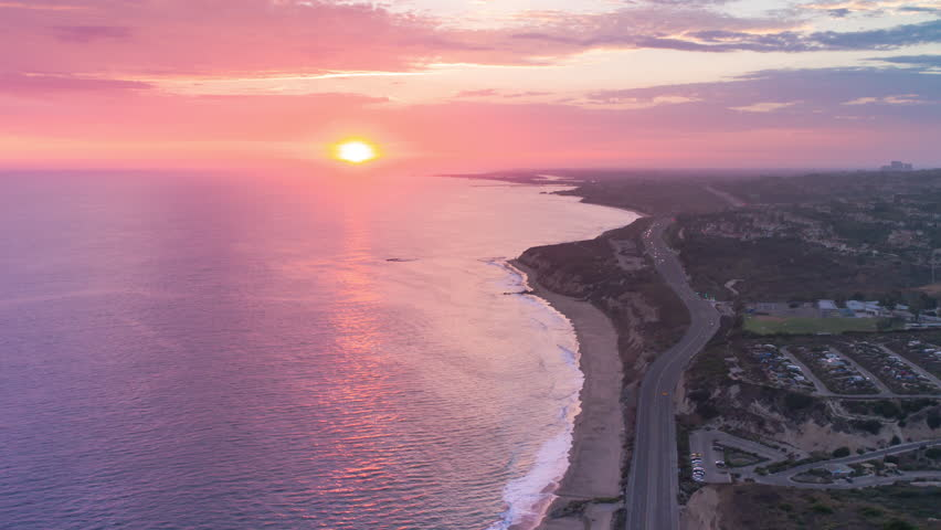 Aerial timelapse in motion (hyperlapse) shot from above at sunset with a drone over the Pacific ocean, Pacific Coast Highway (PCH) with traffic and beach with pink, orange and red skies at twilight.