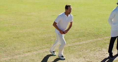 Caucasian bowler delivering ball during match on cricket field