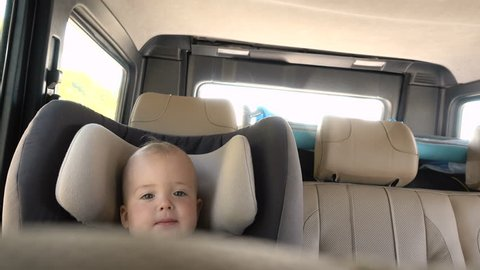 Little baby in booster chair in car