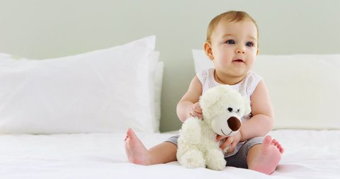 Cute baby girl playing with soft toy on bed in bedroom