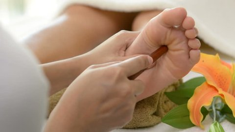 Professional therapist giving relaxing reflexology Thai foot massage with stick to a woman in spa