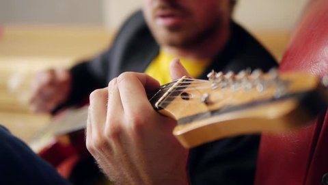Guitarists hands playing song on electric guitar