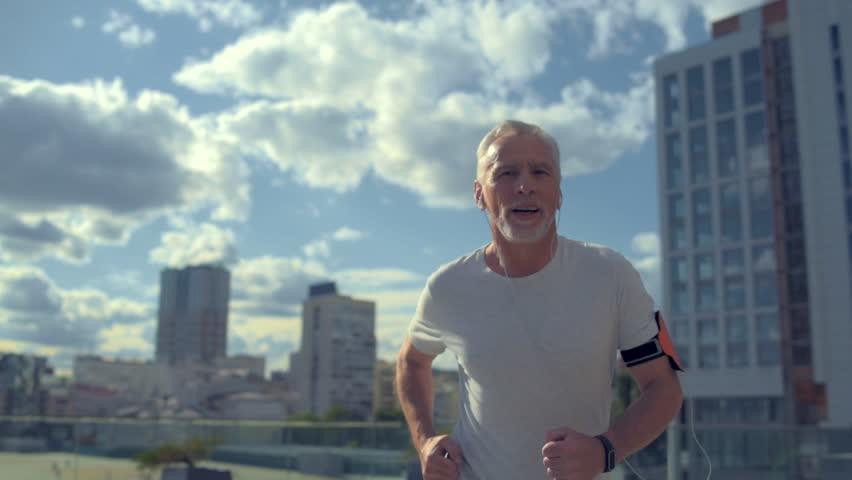 Cheerful senior man running in the urban surrounding
