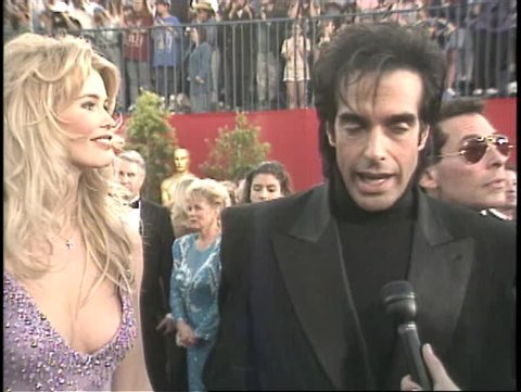 Los angeles, ca - march 27, 1995: david copperfield, claudia schiffer,  walks the red carpet at the academy awards 1995 held at the shrine  auditorium