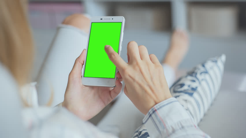 Young Woman in white jeans laying on couch uses SmartPhone with pre-keyed green screen. Few types of gestures - scrolling up and down, tapping, zoom in and out. Perfect for screen compositing   Shutterstock HD Video #29241526