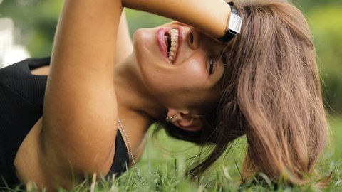 Attractive woman lying on grass at summertime, she relax, coquettish and laughing