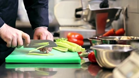 cooking, profession, vegetarian, food and people concept - hands of male chef cook with knife chopping celery on cutting board in kitchen