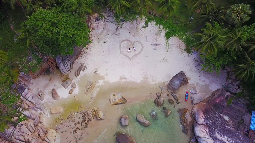 Aerial view from the drone,romantic couple in love lie in the heart shape on the sand beach of Thailand