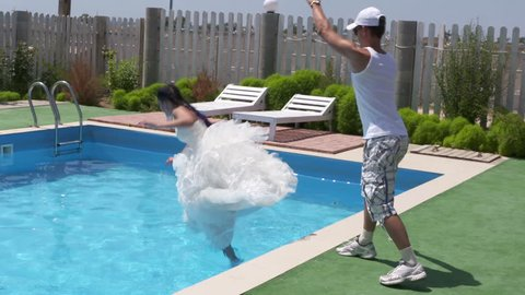Man pushes young bride from poolside into water as a funny joke. Girl in white wedding dress falls into the pool while trying to pose for camera. Bride falling with splashes in slow motion.