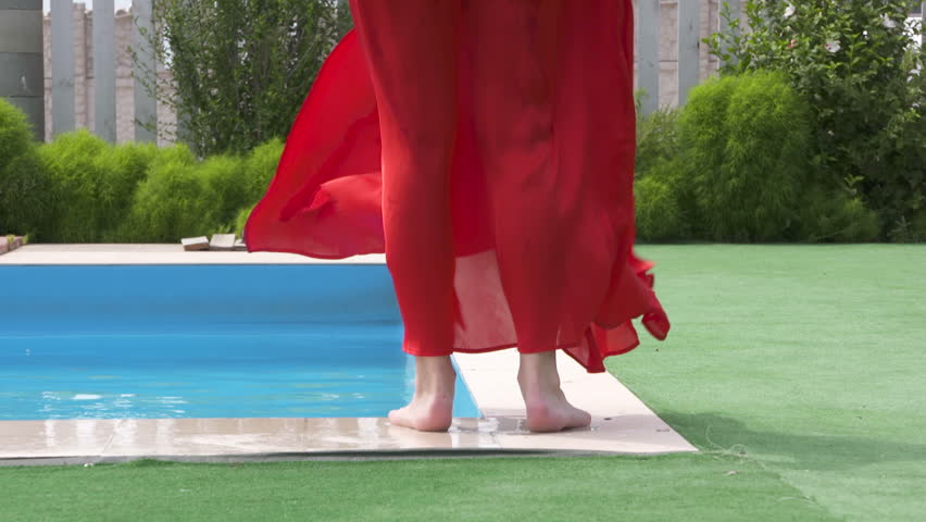Young girl in long red dress walking along swimming pool. Dress fluttering in the wind. Legs of barefoot woman walking away in slow motion. | Shutterstock HD Video #29293306