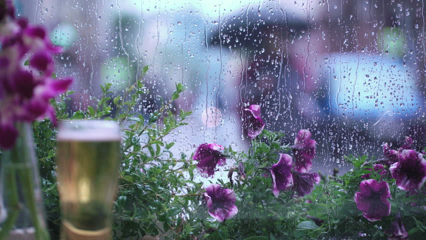 Rain outside the window of the café. A glass of beer. Raindrops on window glass, beautiful bokeh behind a wet city window. Abstract silhouettes of people walking under umbrellas. Concept of lifestyle